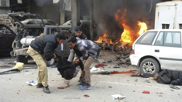 ATTENTION EDITORS - VISUAL COVERAGE OF SCENES OF INJURY OR DEATH Policemen and a resident move a dead body from the site of an explosion outside the police headquarters, in Lahore February 17, 2015. At least seven people died on Tuesday in a large explosion and gunfire at the regional police headquarters in Pakistan's eastern city of Lahore, police said. REUTERS/Imran Sheikh (PAKISTAN - Tags: CIVIL UNREST CRIME LAW) TEMPLATE OUT